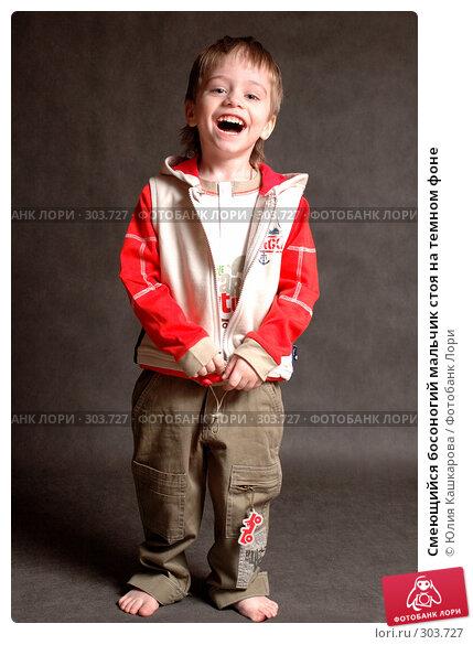 Купить «Смеющийся босоногий мальчик стоя на темном фоне», фото № 303727, снято 23 марта 2008 г. (c) Юлия Кашкарова / Фотобанк Лори