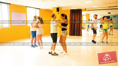 Купить «Smiling adults dancing salsa together in dance studio», видеоролик № 27385399, снято 6 июля 2017 г. (c) Яков Филимонов / Фотобанк Лори
