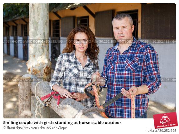 Купить «Smiling couple with girth standing at horse stable outdoor», фото № 30252195, снято 4 июля 2018 г. (c) Яков Филимонов / Фотобанк Лори