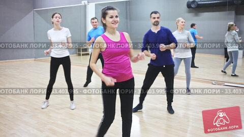 Smiling dancing people practicing bachata movements in dance studio for adults. Стоковое видео, видеограф Яков Филимонов / Фотобанк Лори