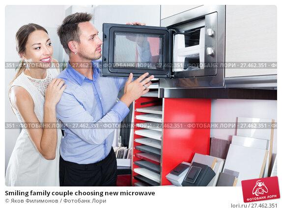 Купить «Smiling family couple choosing new microwave», фото № 27462351, снято 15 июня 2017 г. (c) Яков Филимонов / Фотобанк Лори