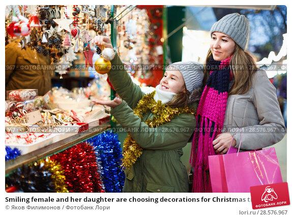 Купить «Smiling female and her daughter are choosing decorations for Christmas tree in the market outdoor.», фото № 28576967, снято 19 декабря 2017 г. (c) Яков Филимонов / Фотобанк Лори