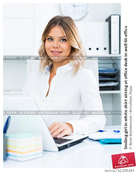 Купить «Smiling girl in white shirt sitting at office desk in well-lit office», фото № 32270651, снято 17 октября 2017 г. (c) Яков Филимонов / Фотобанк Лори