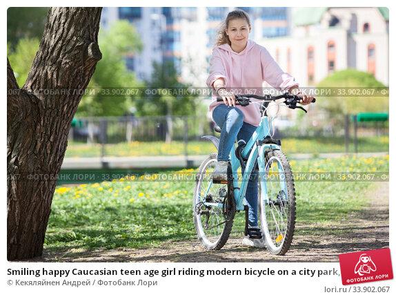 Smiling happy Caucasian teen age girl riding modern bicycle on a city park, looking at camera. Стоковое фото, фотограф Кекяляйнен Андрей / Фотобанк Лори