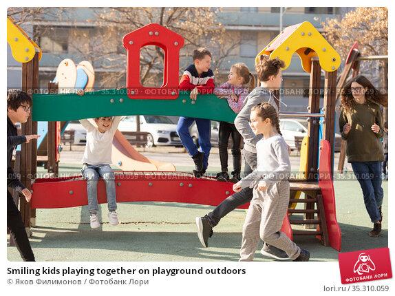 Smiling kids playing together on playground outdoors. Стоковое фото, фотограф Яков Филимонов / Фотобанк Лори