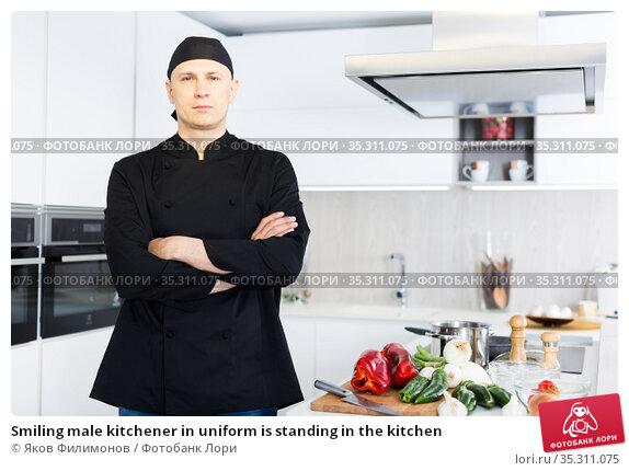 Smiling male kitchener in uniform is standing in the kitchen. Стоковое фото, фотограф Яков Филимонов / Фотобанк Лори