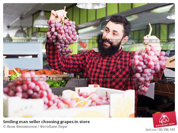 Купить «Smiling man seller choosing grapes in store», фото № 30196191, снято 15 ноября 2016 г. (c) Яков Филимонов / Фотобанк Лори