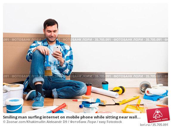 Smiling man surfing internet on mobile phone while sitting near wall... Стоковое фото, фотограф Zoonar.com/Khakimullin Aleksandr D9 / easy Fotostock / Фотобанк Лори