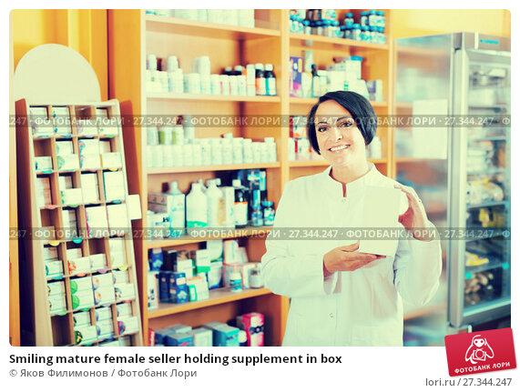Купить «Smiling mature female seller holding supplement in box», фото № 27344247, снято 16 октября 2018 г. (c) Яков Филимонов / Фотобанк Лори