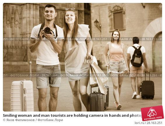Купить «Smiling woman and man tourists are holding camera in hands and photographing», фото № 28163251, снято 22 июня 2017 г. (c) Яков Филимонов / Фотобанк Лори