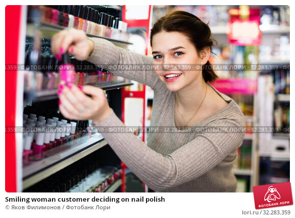 Купить «Smiling woman customer deciding on nail polish», фото № 32283359, снято 21 февраля 2017 г. (c) Яков Филимонов / Фотобанк Лори