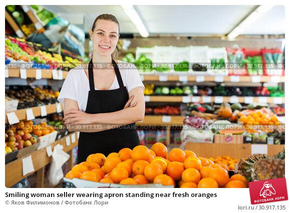 Купить «Smiling woman seller wearing apron standing near fresh oranges», фото № 30917135, снято 27 апреля 2019 г. (c) Яков Филимонов / Фотобанк Лори