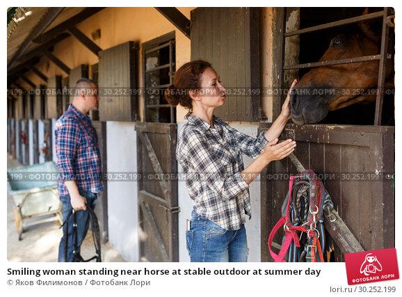 Купить «Smiling woman standing near horse at stable outdoor at summer day», фото № 30252199, снято 4 июля 2018 г. (c) Яков Филимонов / Фотобанк Лори