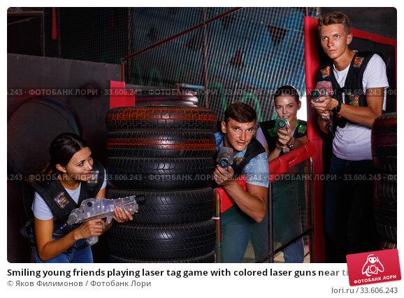 Купить «Smiling young friends playing laser tag game with colored laser guns near tires in labyrinth», фото № 33606243, снято 23 августа 2018 г. (c) Яков Филимонов / Фотобанк Лори