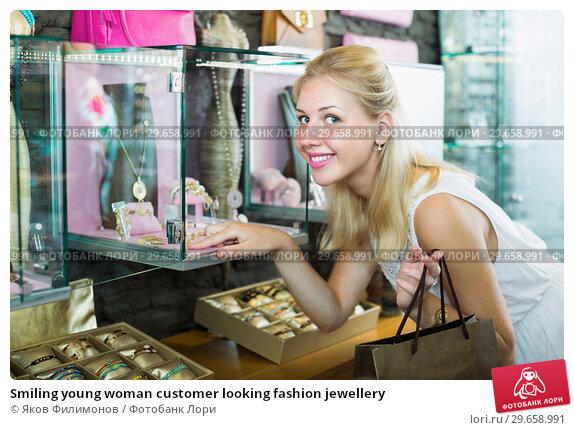 Купить «Smiling young woman customer looking fashion jewellery», фото № 29658991, снято 25 марта 2019 г. (c) Яков Филимонов / Фотобанк Лори