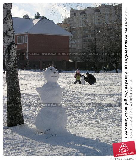 Снеговик, стоящий под деревом; на заднем плане ребенок с папой лепят снеговика, фото № 193059, снято 3 февраля 2008 г. (c) Антон Алябьев / Фотобанк Лори