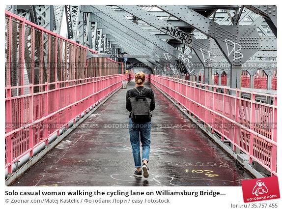 Solo casual woman walking the cycling lane on Williamsburg Bridge... Стоковое фото, фотограф Zoonar.com/Matej Kastelic / easy Fotostock / Фотобанк Лори