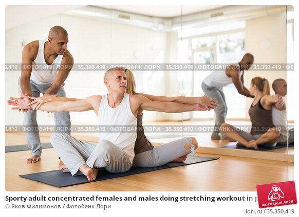 Sporty adult concentrated females and males doing stretching workout in pairs during group training. Стоковое фото, фотограф Яков Филимонов / Фотобанк Лори