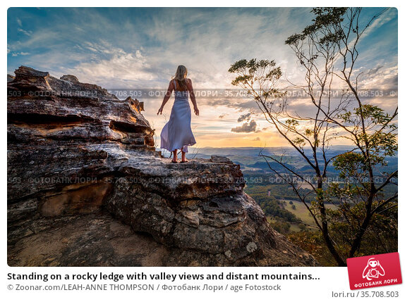 Standing on a rocky ledge with valley views and distant mountains... Стоковое фото, фотограф Zoonar.com/LEAH-ANNE THOMPSON / age Fotostock / Фотобанк Лори
