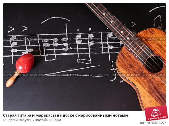 Старая гитара и маракасы на доске с нарисованными нотами. Стоковое фото, фотограф Сергей Лабутин / Фотобанк Лори