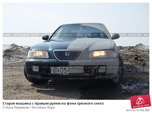 Старая машина с правым рулем на фоне грязного снега (2013 год). Редакционное фото, фотограф Илья Пермяков / Фотобанк Лори