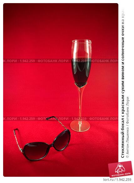 Стеклянный бокал с красным сухим вином и солнечные очки на красном фоне. Стоковое фото, фотограф Антон Ляшенко / Фотобанк Лори