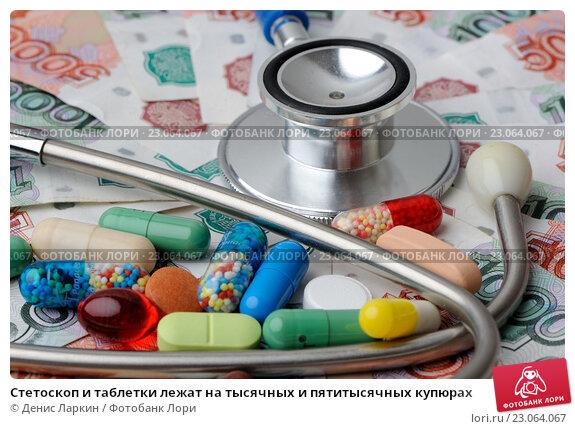 Купить «Стетоскоп и таблетки лежат на тысячных и пятитысячных купюрах», фото № 23064067, снято 2 июня 2016 г. (c) Денис Ларкин / Фотобанк Лори