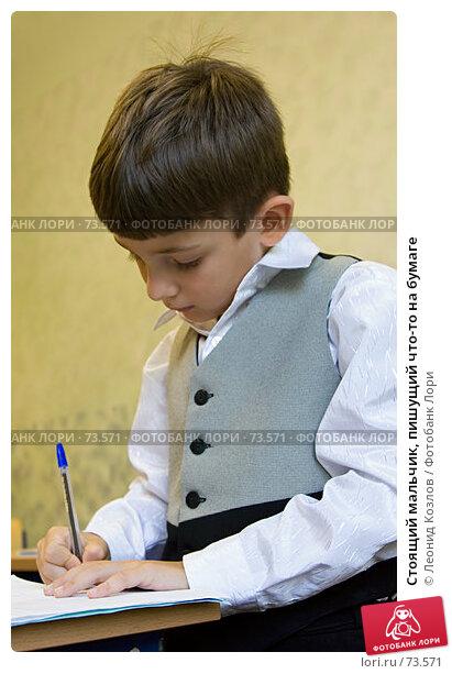 Стоящий мальчик, пишущий что-то на бумаге, фото № 73571, снято 24 мая 2017 г. (c) Леонид Козлов / Фотобанк Лори