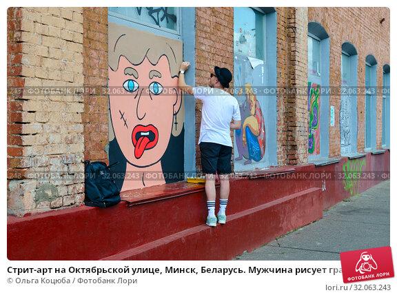 Стрит-арт на Октябрьской улице, Минск, Беларусь. Мужчина рисует граффити на стене промышленного здания (2019 год). Редакционное фото, фотограф Ольга Коцюба / Фотобанк Лори