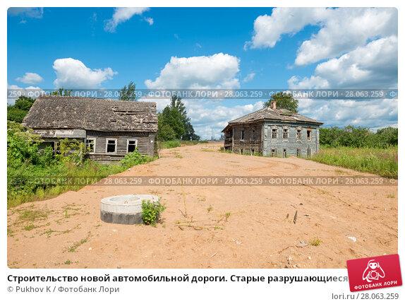 Купить «Строительство новой автомобильной дороги. Старые разрушающиеся выселенные дома на обочине», фото № 28063259, снято 3 августа 2016 г. (c) Pukhov K / Фотобанк Лори