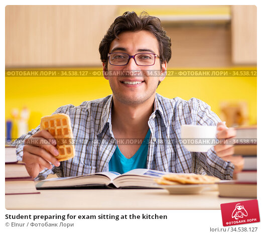 Student preparing for exam sitting at the kitchen. Стоковое фото, фотограф Elnur / Фотобанк Лори