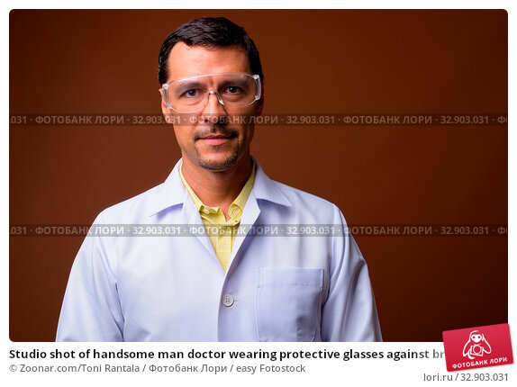 Studio shot of handsome man doctor wearing protective glasses against brown background. Стоковое фото, фотограф Zoonar.com/Toni Rantala / easy Fotostock / Фотобанк Лори