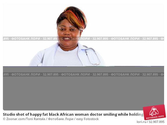 Studio shot of happy fat black African woman doctor smiling while holding slice of watermelon. Стоковое фото, фотограф Zoonar.com/Toni Rantala / easy Fotostock / Фотобанк Лори