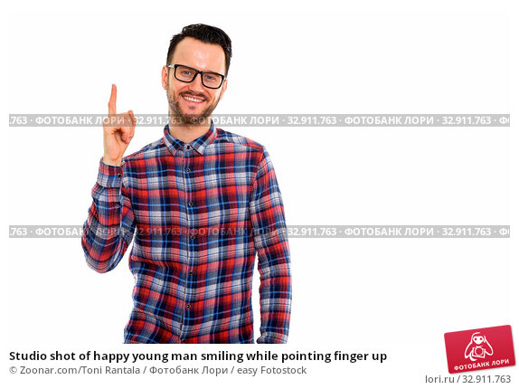Studio shot of happy young man smiling while pointing finger up. Стоковое фото, фотограф Zoonar.com/Toni Rantala / easy Fotostock / Фотобанк Лори