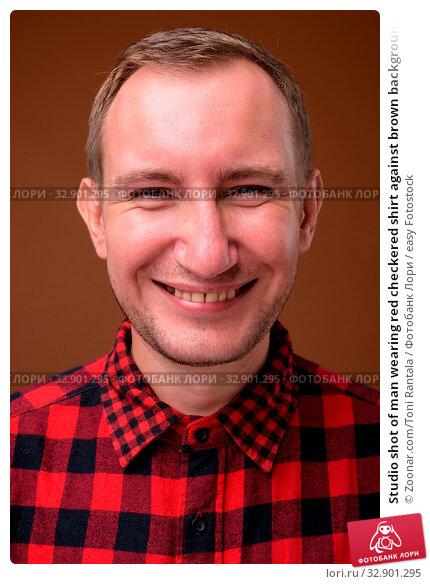 Studio shot of man wearing red checkered shirt against brown background. Стоковое фото, фотограф Zoonar.com/Toni Rantala / easy Fotostock / Фотобанк Лори