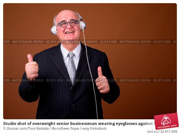 Studio shot of overweight senior businessman wearing eyeglasses against brown background. Стоковое фото, фотограф Zoonar.com/Toni Rantala / easy Fotostock / Фотобанк Лори