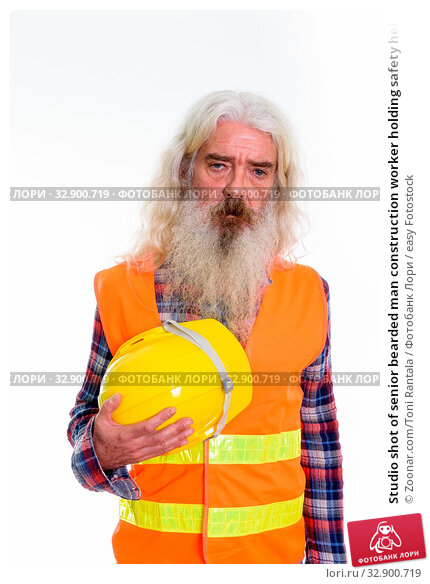 Studio shot of senior bearded man construction worker holding safety helmet. Стоковое фото, фотограф Zoonar.com/Toni Rantala / easy Fotostock / Фотобанк Лори