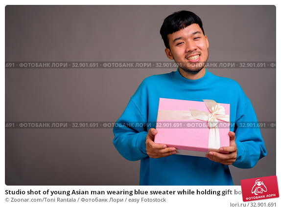 Studio shot of young Asian man wearing blue sweater while holding gift box against gray background. Стоковое фото, фотограф Zoonar.com/Toni Rantala / easy Fotostock / Фотобанк Лори