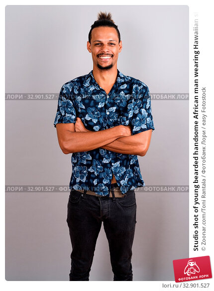 Studio shot of young bearded handsome African man wearing Hawaiian shirt with hair tied against gray background. Стоковое фото, фотограф Zoonar.com/Toni Rantala / easy Fotostock / Фотобанк Лори