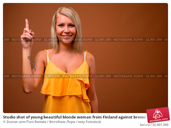 Studio shot of young beautiful blonde woman from Finland against brown background. Стоковое фото, фотограф Zoonar.com/Toni Rantala / easy Fotostock / Фотобанк Лори