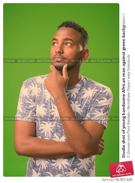 Studio shot of young handsome African man against green background. Стоковое фото, фотограф Zoonar.com/Toni Rantala / easy Fotostock / Фотобанк Лори