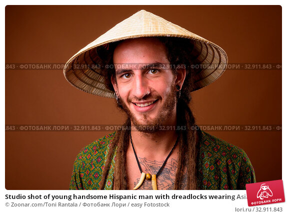 Studio shot of young handsome Hispanic man with dreadlocks wearing Asian style conical hat against brown background. Стоковое фото, фотограф Zoonar.com/Toni Rantala / easy Fotostock / Фотобанк Лори