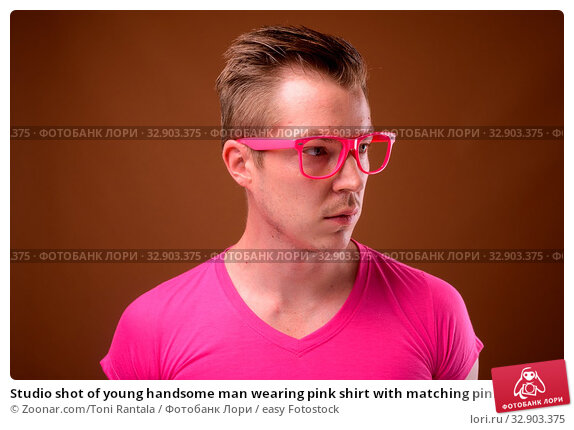 Studio shot of young handsome man wearing pink shirt with matching pink eyeglasses against brown background. Стоковое фото, фотограф Zoonar.com/Toni Rantala / easy Fotostock / Фотобанк Лори