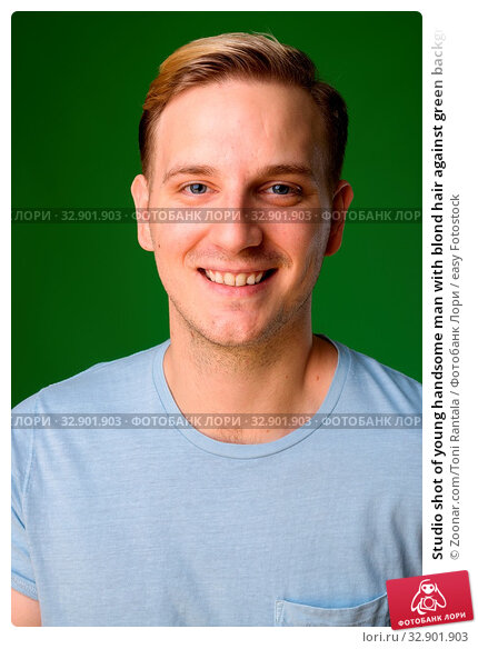Studio shot of young handsome man with blond hair against green background. Стоковое фото, фотограф Zoonar.com/Toni Rantala / easy Fotostock / Фотобанк Лори