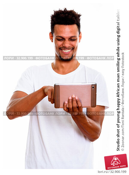 Studio shot of young happy African man smiling while using digital tablet. Стоковое фото, фотограф Zoonar.com/Toni Rantala / easy Fotostock / Фотобанк Лори