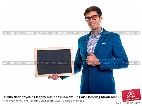 Studio shot of young happy businessman smiling and holding blank blackboard while giving thumb up. Стоковое фото, фотограф Zoonar.com/Toni Rantala / easy Fotostock / Фотобанк Лори