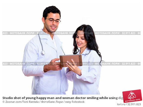 Studio shot of young happy man and woman doctor smiling while using digital tablet together. Стоковое фото, фотограф Zoonar.com/Toni Rantala / easy Fotostock / Фотобанк Лори
