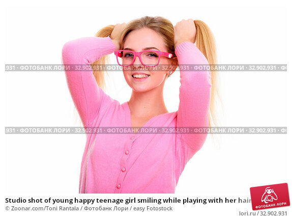 Studio shot of young happy teenage girl smiling while playing with her hair to pigtails. Стоковое фото, фотограф Zoonar.com/Toni Rantala / easy Fotostock / Фотобанк Лори