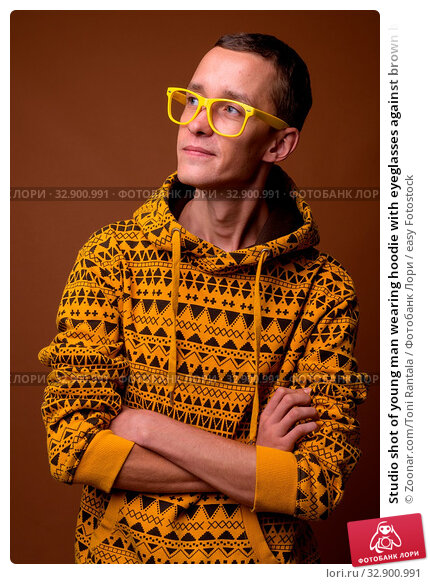 Studio shot of young man wearing hoodie with eyeglasses against brown background. Стоковое фото, фотограф Zoonar.com/Toni Rantala / easy Fotostock / Фотобанк Лори