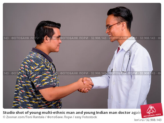 Studio shot of young multi-ethnic man and young Indian man doctor against gray background. Стоковое фото, фотограф Zoonar.com/Toni Rantala / easy Fotostock / Фотобанк Лори